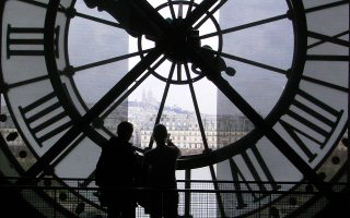 Φωτογραφία αρχείου με ημερομηνία 17 Μαρτίου 2007 απεικονίζει δύο νέους κάτω από ένα γιγάντιο ρολόι στο Μουσείο Ορσέ του Παρισιού. Τα ξημερώματα της 25ης Οκτωβρίου οι δείοκτες των ρολογιών θα μετακινηθούν μία ώρα .