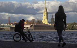 People walk along the embankment of the Neva River in St. Petersburg, Russia, Friday, Sept. 28, 2018. St. Peter and St. Paul Cathedral is in the background. (AP Photo/Dmitri Lovetsky)