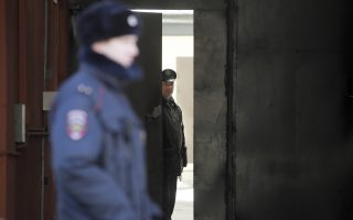 A member of security looks out from the U.S. consulate as a Russian police officer guards the entrance, in St. Petersburg, Russia, Friday, March 30, 2018. Russia announced the expulsion of more than 150 diplomats, including 60 Americans, on Thursday and said it was closing a U.S. consulate in retaliation for the wave of Western expulsions of Russian diplomats over the poisoning of an ex-spy and his daughter in Britain, a tit-for-tat response that intensified the Kremlin's rupture with the United States and Europe. (AP Photo/Dmitri Lovetsky)
