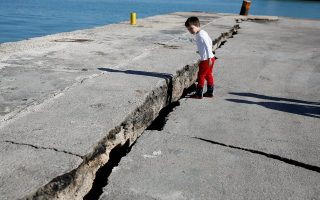 A child looks at the damaged pier of the port of Zakynthos, following an earthquake off the island of Zakynthos,Greece, October 26, 2018. REUTERS/Costas Baltas