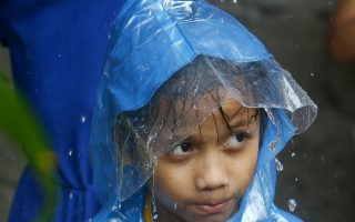 A boy stays under a dripping tarpaulin amidst a downpour brought about by Typhoon Yutu which made a landfall in northeastern Philippines Tuesday, Oct. 30, 2018 in suburban Pasay city, south of Manila, Philippines. A strong typhoon battered the northern Philippines on Tuesday, though officials were hopeful that successful evacuations would help avoid a repeat of the death and destruction wrought by a powerful storm last month. (AP Photo/Bullit Marquez)