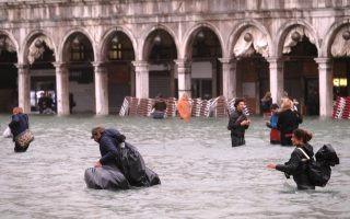 People walk in a flooded Saint Mark Square during a period of seasonal high water in Venice, Italy October 29, 2018 Reuters/Manuel Silvestri
