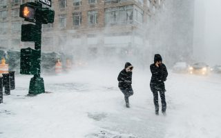 epa07078115 People walk in the street in New York, New York, USA, 04 January 2018. A Nor'easter snow storm is expected to bring up to 8 inches (20 cm) of snow in the New York area.  EPA/ALBA VIGARAY
