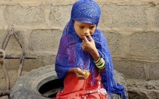 In this Aug. 25, 2018 photo, a girl eats boiled leaves from a local vine to stave off starvation, in the extremely impoverished district of Aslam, Hajjah, Yemen. The situation in Aslam district is a sign of the holes in an international aid system that is already overwhelmed but is the only thing standing between Yemen's people and massive death from starvation amid the country's 3-year civil war. (AP Photo/Hammadi Issa)