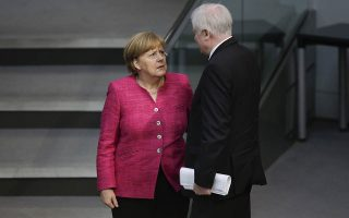 FILE - In this May 15, 2018 file photo German Chancellor Angela Merkel, left, talks with German Interior Minister Horst Seehofer, right, during the first day of the budget 2018 debate at the parliament Bundestag at the Reichstag building in Berlin, Tuesday, May 15, 2018. (AP Photo/Markus Schreiber)
