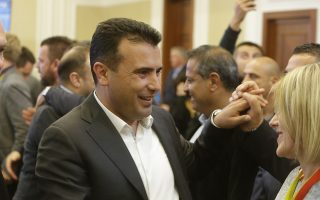 Macedonia's Prime Minister Zoran Zaev talks to a colleague following a news conference about the referendum in Skopje, Macedonia, late Sunday, Sept. 30, 2018. Zaev has described the crucial referendum on changing the small European country's name to North Macedonia and thereby pave the way to NATO membership as a clear success, despite lower than hoped for voter turnout. Zaev said he had no intention of resigning as the