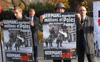 «Γερμανοί, καταστρέψατε την Πολωνία, τώρα πρέπει να πληρώσετε», γράφει το πανό του διαδηλωτή.
