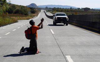 Ικέτης. Σε στάση παράκλησης για μια μεταφορά με αυτοκίνητο, είναι  ο άνδρας στην μέση του δρόμου. Ενας από τους εκατοντάδες πρόσφυγες της Λατινικής Αμερικής που ταξιδεύουν με την ελπίδα να μπουν στις ΗΠΑ. Η  φωτογραφία από αυτοκινητόδρομο στα προάστια της Γκουνταλαχάρα του Μεξικού.  REUTERS/Go Nakamura