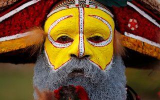 Τον Κινέζο. Ντυμένος και βαμμένος με τα χρώματα της φυλής του ένας χορευτής από την Παπούα  Νέα Γουινέα περιμένει την άφιξη του προέδρου Σι με αφορμή την Σύνοδο του APEC στο Πορτ Μορέσμπι. REUTERS/David Gray