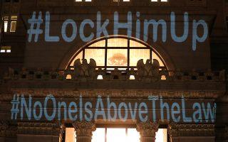 «Κλείστε τον μέσα – Κανένας δεν είναι πάνω από τον νόμο» γράφει το σύνθημα που προβάλλεται πάνω στο δημαρχείο της Οκλαχόμα, όπου ακτιβιστές διαδήλωσαν εναντίον της απόφασης Τραμπ να αναθέσει την επίβλεψη της έρευνας Μιούλερ στον πιστό του υπηρεσιακό υπουργό Δικαιοσύνης Μάθιου Γουίτακερ.