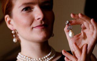 Μοντέλο κρατάει στο χέρι του το μενταγιόν από φυσικά μαργαριτάρια και διαμάντια το οποίο πωλήθηκε αντί 36 εκατ. δολαρίων.
