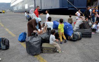 Οικογένειες προσφύγων και μεταναστών στο λιμάνι της Μυτιλήνης περιμένουν να επιβιβαστούν στο πλοίο για τον Πειραιά.