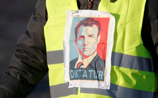 A man wearing a yellow vest, a symbol of a French drivers' protest against higher fuel prices, attends the demonstration with an image of French president Emmanuel Macron, in Paris, France, November 17, 2018. REUTERS/Charles Platiau