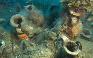 FILE - In this Wednesday, July 19, 2017 file photo, marine life grows on ancient North African amphorae at the site of a 4th century A.D. shipwreck off the coast of Albania. On the seabed off the rugged shores of Albania, one of the world's least explored underwater coastlines, lies a wealth of treasures, and researchers are urging Albanian authorities to build a museum to display the artefacts. (AP Photo/Geo Delveroudis, FILE)