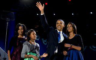 Μαζί με την πρώτη κυρία, Μισέλ Ομπάμα, και τις δύο κόρες του, Μάλια και Σάσα, ο πρόεδρος των Ηνωμένων Πολιτείων, Μπάρακ Ομπάμα, χαιρετάει τους υποστηρικτές του κατά τη διάρκεια του πάρτι για τον εορτασμό της επανεκλογής του στο προεδρικό αξίωμα, μετά τη νίκη του στις προεδρικές εκλογές επί του Μιτ Ρόμνεϊ, το 2012. (AP Photo/Carolyn Kaster)
