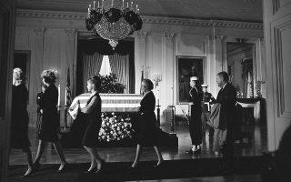 Μέλη του προσωπικού του Λευκού Οίκου περνούν μπροστά από το σκεπασμένο με την αμερικανική σημαία φέρετρο του δολοφονημένου 35ου προέδρου των Ηνωμένων Πολιτειών, Τζον Φιτζέραλντ Κένεντι, στο ανατολικό δωμάτιο του Λευκού Οίκου, το 1963. (AP Photo/Henry Burroughs)