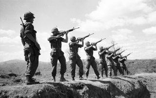 Άνδρες της 173ης Αερομεταφερόμενης Ομάδας Μάχης Αλεξιπτωτιστών του αμερικανικού στρατού πυροβολούν με τα τυφέκια τους τρεις φορές στον αέρα, τιμώντας τους νεκρούς συναδέλφους τους, οι οποίοι έπεσαν στη μάχη της Ντακ Το εναντίον των Βιετ Κονγκ και του Λαϊκού Στρατού του Βόρειου Βιετνάμ, το 1967. (AP Photo/Rick Merron)