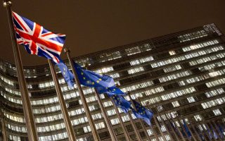 The Union Flag and EU flags flap in the wind in the early morning outside of an EU summit in Brussels, Sunday, Nov. 25, 2018. The European Union removed the last major obstacle to sealing an agreement on Brexit after Spain said it had reached a deal with Britain over Gibraltar. (AP Photo/Virginia Mayo)
