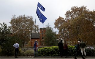An anti-Brexit supporter holds European flags overlooking College Green near the Houses of Parliament in London, Thursday Nov. 15, 2018. Leading Brexiteer Jacob Rees-Mogg has submitted a letter of no confidence in Theresa May, as the Prime Minister reels from the loss of four ministers - including two from her Cabinet - in protest at her Brexit plans. (AP Photo/Matt Dunham)