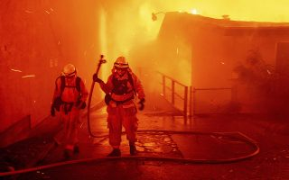 Firefighters battle the Camp Fire as it tears through Paradise, Calif., on Thursday, Nov. 8, 2018. Tens of thousands of people fled a fast-moving wildfire Thursday in Northern California, some clutching babies and pets as they abandoned vehicles and struck out on foot ahead of the flames that forced the evacuation of an entire town and destroyed hundreds of structures. (AP Photo/Noah Berger)