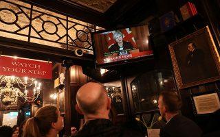 Πελάτες σε παμπ του Λονδίνου παρακολουθούν σε τηλεόραση την Τερέζα Μέι να κάνει δηλώσεις για το Brexit. Ο πίνακας δεξιά εικονίζει τον Ντισραέλι.