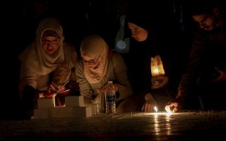 Jordanians light candles that form the Earth Hour logo, in an official attempt to be registered in the Guinness Book of Records for the largest candle-shaped World Hour logo, in Amman, Jordan, Saturday, March 24, 2018. (AP Photo/Raad Adayleh)