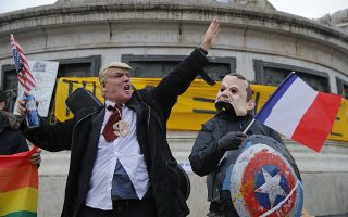People wearing a Donald Trump mask, left, and an Emmanuel Macron mask act up for the cameras during an anti-Trump gathering in Republique square in Paris, Sunday Nov. 11, 2018. President Donald Trump joined other international leaders in Paris to mark the 100th anniversary of the Armistice that ended World War I. (AP Photo/Vadim Ghirda)