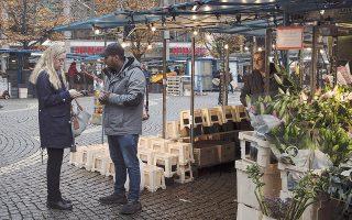 Μια Σουηδή αγοράζει με κάρτα άνθη σε ένα υπαίθριο κατάστημα λουλουδιών στη Στοκχόλμη. Στα επόμενα έξι χρόνια, ένας στους δύο καταστηματάρχες στη σκανδιναβική χώρα θα σταματήσει να δέχεται μετρητά.