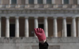 Μία καθαρίστρια του Υπουργείου Οικονομικών υψώνει το χέρι της καθώς φωνάζει συνθήματα μπροστά από τη Βουλή, την Τρίτη 25 Νοεμβρίου 2014. Οι 595 καθαρίστριες πραγματοποιούν πορεία αλληλεγγύης με αφορμή την 25η Νοέμβρη, παγκόσμια μέρα για την εξάλειψη της βίας κατά των γυναικών, για την υποστήριξή σε γυναίκες θύματα βίας στο δρόμο, στην οικογένεια, στην δουλειά και έχουν καλέσει  όλες τις γυναίκες στο  Σύνταγμα, για περπατήσουν μαζί  595 κόκκινα βήματα. ΑΠΕ-ΜΠΕ/ΑΠΕ-ΜΠΕ/ΓΙΑΝΝΗΣ ΚΟΛΕΣΙΔΗΣ