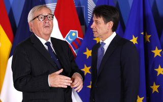 Italian Prime Minister Giuseppe Conte, right, speaks with European Commission President Jean-Claude Juncker during an informal EU summit on migration at EU headquarters in Brussels, Sunday, June 24, 2018. (Yves Herman, Pool Photo via AP)