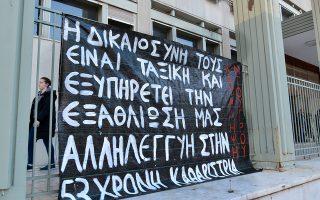 Πανό αναρτημένο έξω από το Δικαστικό Μέγαρο Λάρισας που γράφει: