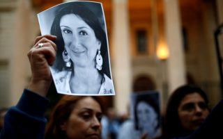 FILE PHOTO: People hold up pictures of assassinated anti-corruption journalist Daphne Caruana Galizia during a vigil and demonstration marking seven months since her murder in a car bomb, at her makeshift memorial outside the Courts of Justice in Valletta, Malta May 16, 2018.  REUTERS/Darrin Zammit Lupi/File Photo