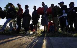 Migrants traveling with a caravan hoping to reach the U.S. border, wait in line to board buses in La Concha, Mexico, Wednesday, Nov. 14, 2018. Buses and trucks are carrying some migrants into the state of Sinaloa along the Gulf of California and further northward into the border state of Sonora. The bulk of the main caravan appeared to be about 1,100 miles from the border, but was moving hundreds of miles per day. (AP Photo/Marco Ugarte)