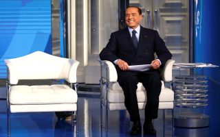 Italy's former Prime Minister Silvio Berlusconi looks on during the taping of the television talk show