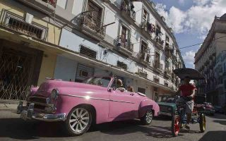 epa06409595 Tourists travel on a classic car through the streets of Havana, Cuba, 29 December 2017. The island expects to close the year with a new tourist record after reaching 4,7 million visitors in 2017.  EPA/ERNESTO MASTRASCUSA