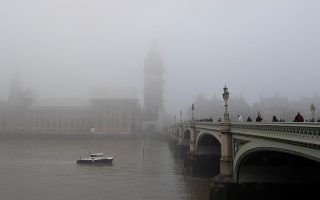 People cross Westminster Bridge as the Houses of Parliament are are shrouded in fog in London, Britain, November 27, 2018.  REUTERS/Toby Melville