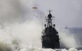 FILE In this file photo taken on Friday, Sept. 9, 2016, Russian navy ships and military paratroopers take a part in a landing operation during military drills at the Black Sea coast, Crimea.  President Vladimir Putin is projecting Russian military power overseas on a scale unseen since Soviet times. A massive reform effort begun in the wake of Russia's troubled 2008 invasion of Georgia has transformed what long were crumbling, demoralized forces into an agile military capable of swift action in Ukraine and Syria. Russia's young men once typically shunned their obligatory military service, but today's recruits talk eagerly of longer-term enlistments. (AP Photo/Pavel Golovkin, File)