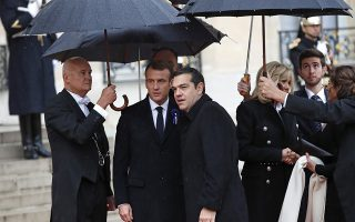 Greece's Prime Minister Alexis Tsipras, center right, is greeted by French President Emmanuel Macron as he arrives at the Elysee Palace in Paris to participate in a World War I Commemoration Ceremony, Sunday Nov. 11, 2018. International leaders are taking place in a ceremony in Paris on Sunday at mark the 100th anniversary of the end of World War I. (AP Photo/Christophe Ena)