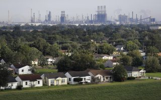 A residential neighborhood sits next to an oil refinery in Port Arthur, Texas, Thursday, Sept. 28, 2017. The region's economy is tied to the petroleum industry more than in any other place in America: the concentration of people here employed by refineries is 81 times higher than the rest of the country. Though research suggests most in Jefferson County believe that humans have contributed to the warming of the globe, many struggle still to know what to expect their leaders to do about it without at the same time crippling their own economy. (AP Photo/David Goldman)