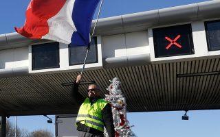 Ακτιβιστής των «Κίτρινων Γιλέκων» υψώνει τη γαλλική σημαία, ενώ άλλοι διαδηλωτές ανοίγουν τις πύλες των διοδίων, κοντά στην Εξ ντε Προβάνς.