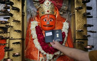 Ο ναός της βίζας. Ο ιερέας βάζει το διαβατήριο ενός ενδιαφερόμενου στο σώμα του θεού Χανουμάν, στον ναό που είναι αφιερωμένος σε αυτόν στο Αχμενταμπάντ της Ινδίας. Εκεί καταφεύγουν όσοι θέλουν να εκκριθεί η βίζα τους για να ταξιδέψουν και να δουλέψουν σε άλλες χώρες.  REUTERS/Amit Dave