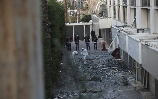 Greek forensic experts search the debris after a powerful bomb exploded outside private Greek television station Skai, in Faliro, Athens, on Monday, Dec, 17, 2018. Police said the blast occurred outside the broadcasters' headquarters near Athens after telephoned warnings prompted authorities to evacuate the building, causing extensive damage but no injuries. (AP Photo/Petros Giannakouris)