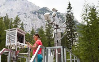 Επιστήμονας παρατηρεί τα στοιχεία που έχει καταγράψει επίγειος μετεωρολογικός σταθμός.
