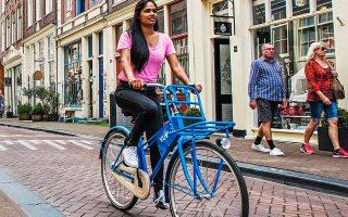 Νεαρή ποδηλάτισσα σε δρόμο του Αμστερνταμ.