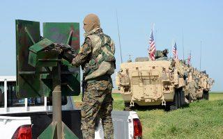 Ανδρας της κουρδικής πολιτοφυλακής YPG δίπλα σε δυνάμεις των ΗΠΑ στη Συρία. Με απόφαση Τραμπ, οι 2.000 Αμερικανοί στρατιώτες θα αποχωρήσουν.