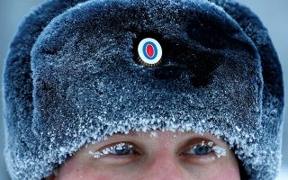 A Russian traffic police officer, whose eyelashes and headwear are covered with hoarfrost, takes part in the