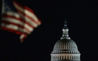 The U.S. Capitol Dome is seen beyond American Flags around the the base of the Washington Monument in Washington, early Saturday, Dec. 22, 2018. The American Flags are at half-staff to honor of former President George H.W. Bush. Hundreds of thousands of federal workers faced a partial government shutdown early Saturday after Democrats refused to meet President Donald Trump's demands for $5 billion to start erecting a border wall with Mexico. Overall, more than 800,000 federal employees would see their jobs disrupted, including more than half who would be forced to continue working without pay. (AP Photo/Carolyn Kaster)