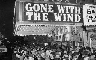 Πλήθος κόσμου έχει συγκεντρωθεί έξω από την κινηματογραφική αίθουσα του Astor Theater στο Broadway, στη Νέα Υόρκη, για να παρακολουθήσουν την πρεμιέρα της επικής ταινίας εποχής του Βίκτορ Φλέμινγκ, «Όσα Παίρνει ο Άνεμος», της μεγαλύτερης κινηματογραφικής εμπορικής επιτυχίας όλων των εποχών, το 1939. (AP Photo)