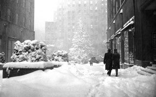 Το εμβληματικό τεράστιο χριστουγεννιάτικο δέντρο του Κέντρου Ροκφέλερ στο Μανχάταν στέκει αγέρωχο και φωτισμένο εν μέσω μίας σφοδρής χιονοθύελλας που έπληξε τη Νέα Υόρκη τις ημέρες των Χριστουγέννων του 1947, τα οποία υπήρξαν από τα πιο «λευκά» που έχει βιώσει η αμερικανική μητρόπολη στην ιστορία της. (AP Photo/Harry Harris)