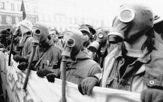Φοιτητές που συμμετέχουν σε μία μαζική συγκέντρωση διαμαρτυρίας 250.000 ατόμων στην πλατεία Βέντσεσλας της Πράγας, φορούν αντιασφυξιογόνες μάσκες, για να εκφράσουν με έναν ιδιαίτερο τρόπο την αντίθεση τους στις εξελίξεις στους κόλπους του κομμουνιστικού καθεστώτος, το οποίο βιώνει τις τελευταίες στιγμές του, ανίκανο να αντιμετωπίσει την αποφασιστικότητα και το πείσμα της «Βελούδινης Επανάστασης», η οποία έδωσε τέλος σε σαράντα χρόνια κομμουνιστής εξουσίας στην τότε Τσεχοσλοβακία, το 1989. (AP Photo/Peter Dejong)